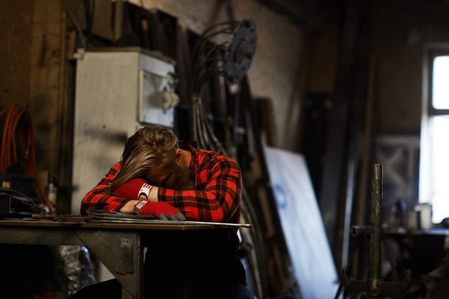 il lavoratore stanco e affaticato che dorme con la testa sulle braccia ad un tavolo in ambiente di lavoro ha bisogno di un po' di riposo per ridurre la fatica