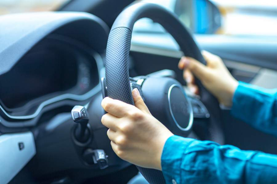 Mani sul volante di un'auto per una guida sicura e sicurezza su strada