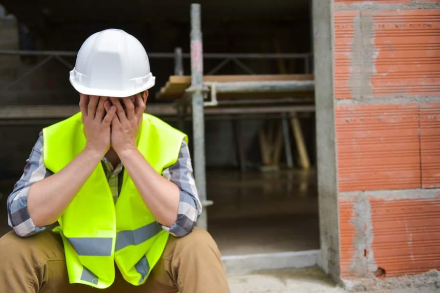 Il lavoratore stanco frustrato con il casco e la maglia di sicurezza bianchi colpisce le sue mani davanti al fronte