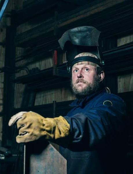 Il saldatore con indumenti protettivi personali con visiera aperta e guanti cerca nella fabbrica