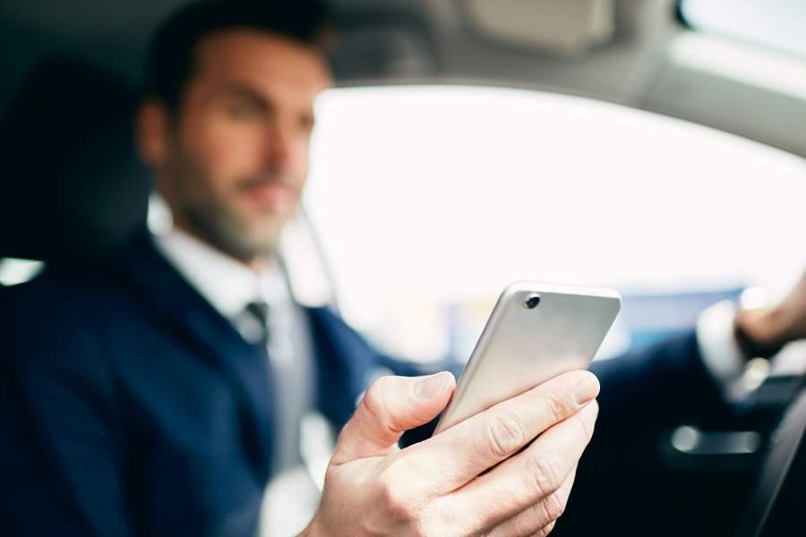 L'uomo in abito si siede al volante di un'auto e guarda il suo smartphone in mano e si lascia distrarre deliberatamente.