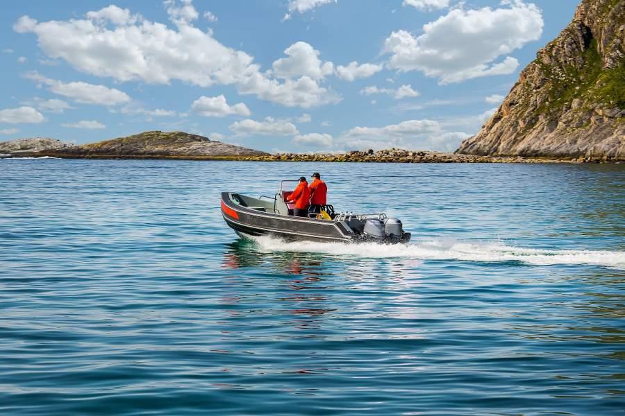 Due uomini stanno uscendo dalla baia su un piccolo motoscafo.