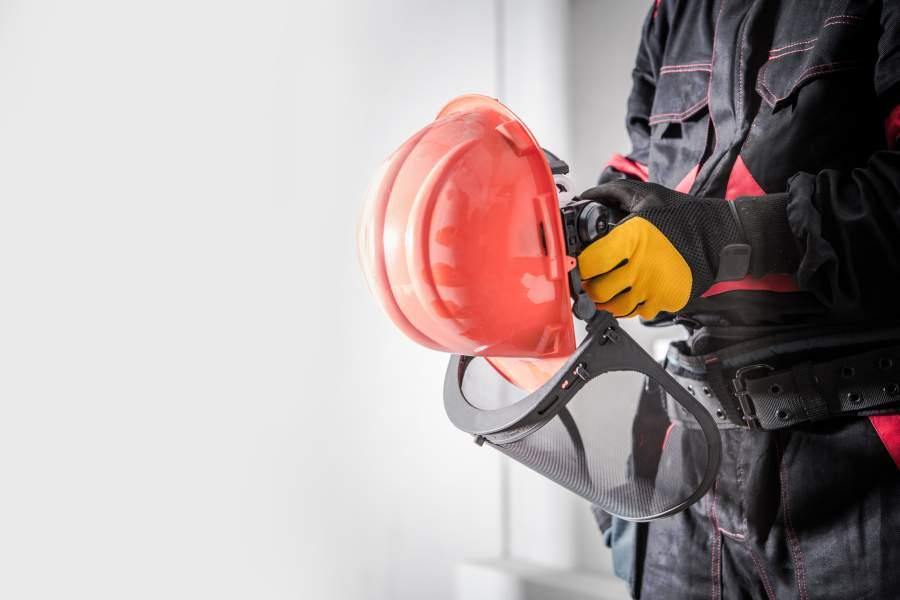 Dipendenti in abiti da lavoro e guanti di sicurezza con il casco arancione con visiera in mano