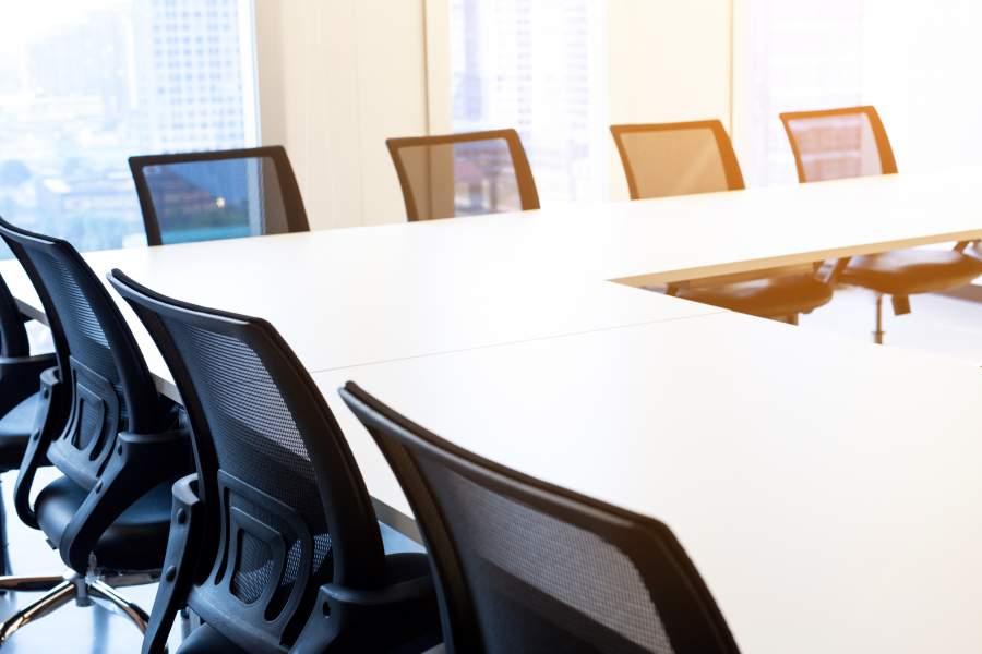 Sedie vuote e comode con schienali neri su tavoli bianchi sopra l'angolo nella formazione del workshop per sessioni di discussione aperte.