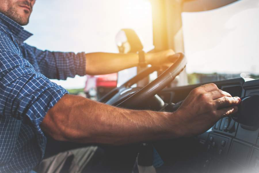 Un uomo con una camicia a quadri guida la macchina e guarda il cruscotto invece di concentrarsi sulla strada.
