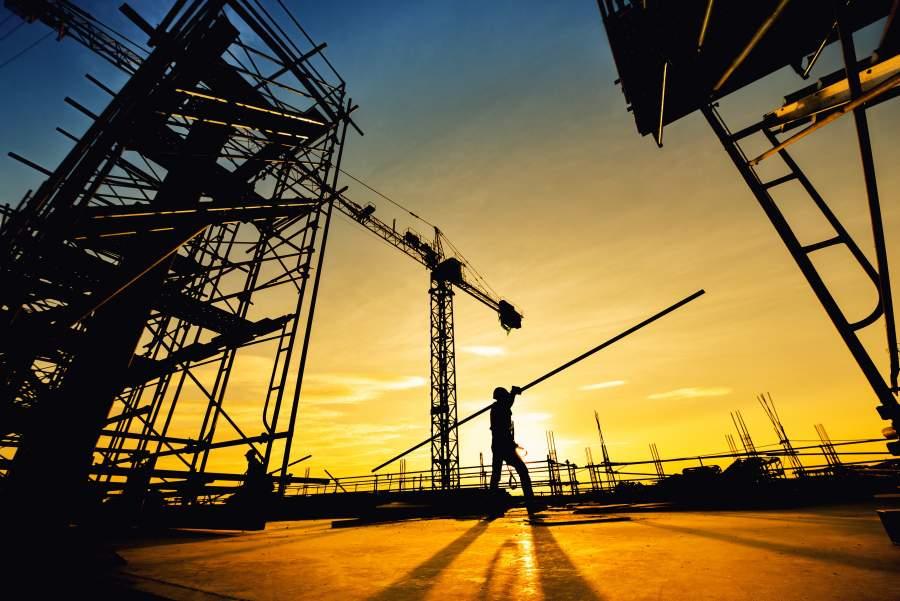 La silhouette di un dipendente che porta una lunga barra di ferro sopra la spalla sopra il cantiere, con il tramonto sullo sfondo.